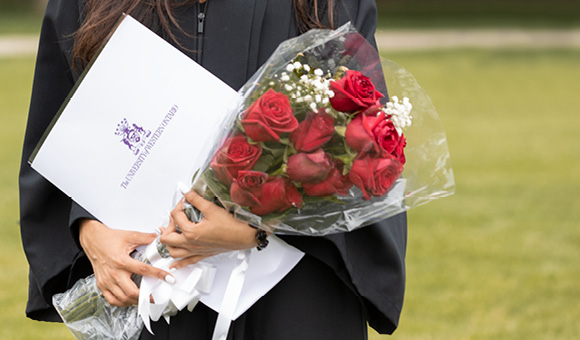 Woman in grad gown holding roses and diploma