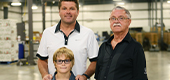 Eric Kints with his son and grandson standing in the warehouse of Huron Produce