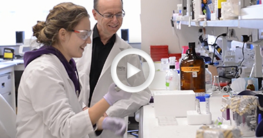 Screenshot of video showing two scientists one female, one male working together at a lab bench