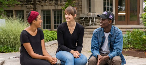 A group of 3 students sitting outside chatting with each other.