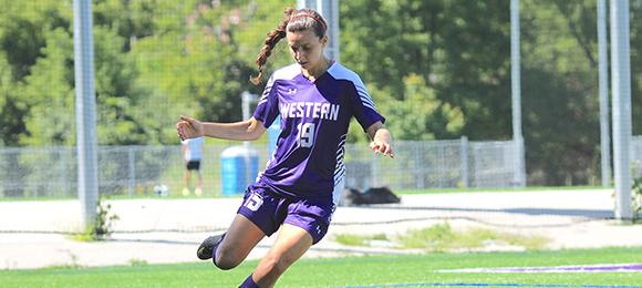 A Western women's soccer player kicks the ball